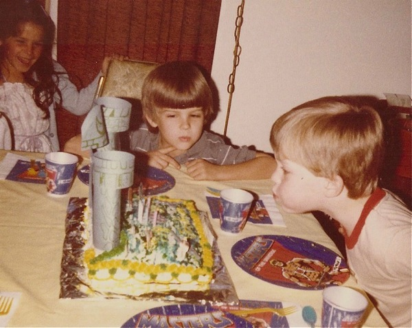 Josh blowing out candles on the Grayskull cake